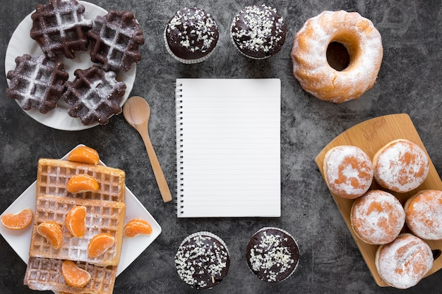 Flat lay of notebook with assortment of doughnuts and waffles