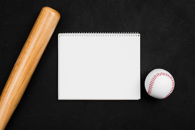 Flat lay of notebook with baseball and bat