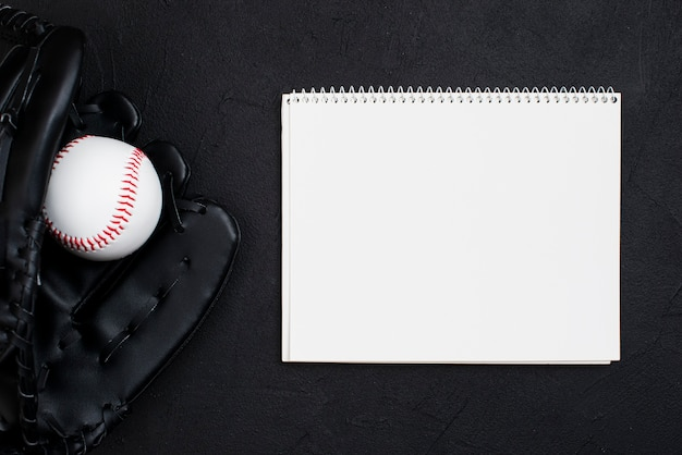 Flat lay of notebook with baseball in glove
