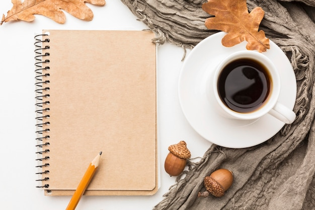 Flat lay of notebook with coffee and autumn leaves