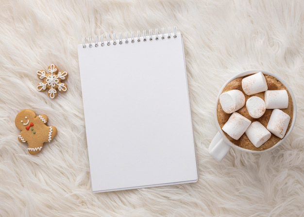 Flat lay of notebook with cup of hot cocoa with marshmallows