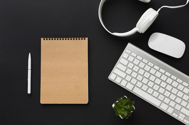 Flat lay of notebook with headphones on desktop