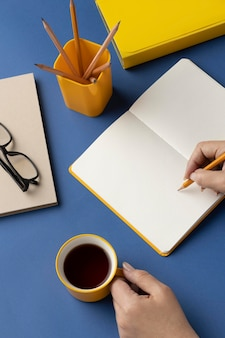 Flat lay notebook with to do list on desk with cup of coffee beside
