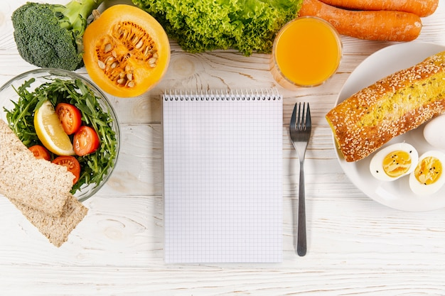 Flat lay of notebook with meals and vegetables