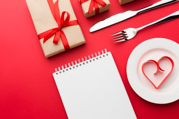 Flat lay of notebook with paper heart shape and cutlery