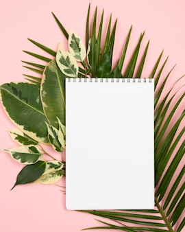 Flat lay of notebook with plant leaves