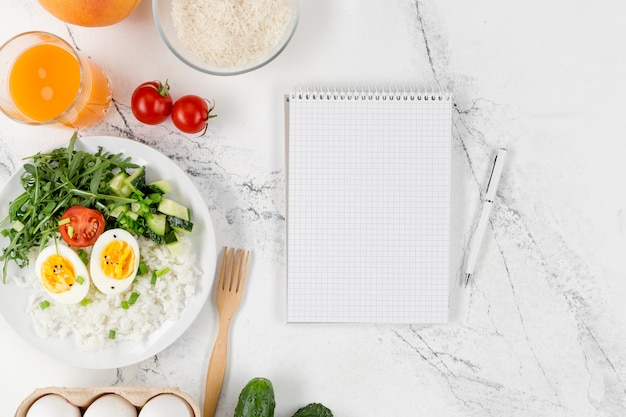 Flat lay of notebook with plate of rice and eggs