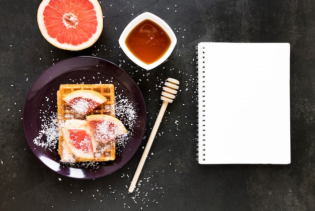 Flat lay of notebook with plate of waffles and citrus