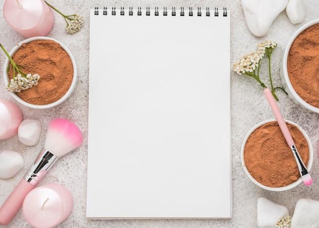 Lay piatto del notebook con polvere in ciotole e pennelli