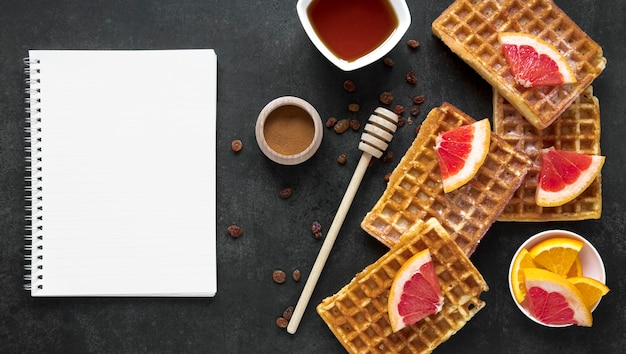 Flat lay of notebook with waffles and citrus