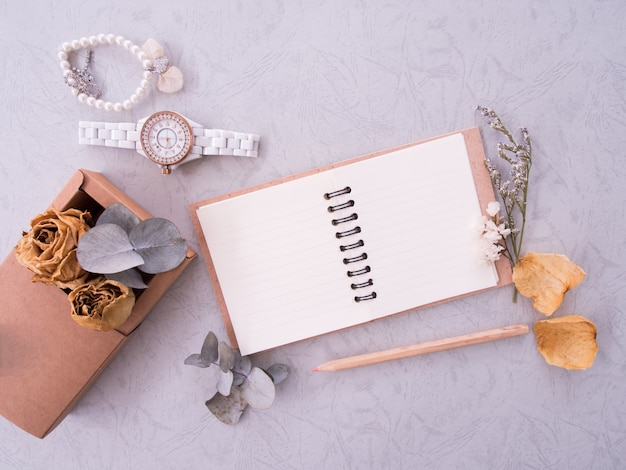 Flat lay of notebook, wristwatch and bracelet on vintage background with copy space
