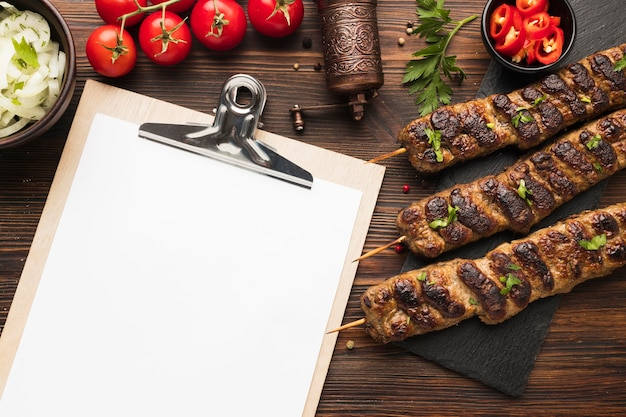 Flat lay of notepad with delicious kebabs and tomatoes