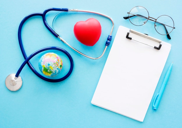 Flat lay of notepad with heart shape and stethoscope