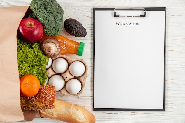 Flat lay of notepad with paper bag with vegetables and bread