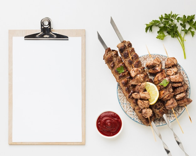 Flat lay of notepad with plate of delicious kebab and ketchup