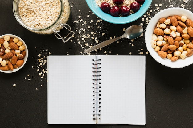 Flat lay nuts mix and oats jar with notebook