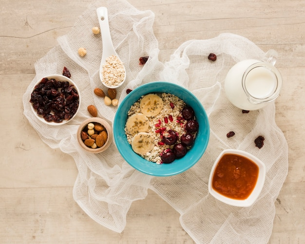 Flat lay oats bowl with fruits nuts and milk