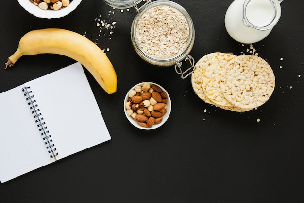 Flat lay oats jar with nuts mix banana and notebook