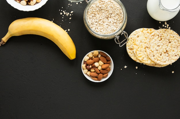 Flat lay oats jar with nuts mix and banana