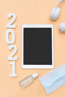 베이지 색 배경에 의료 마스크, 소독제 젤, 헤드폰 및 태블릿으로 2021 목표의 평면 배치