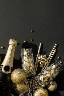 クリスタルグラスの紙吹雪とつまらないものとシャンパンのボトルのフラットレイ