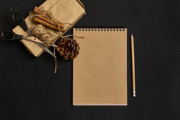 ロープで結ばれたシナモンで飾られた茶色の包装紙のクリスマスプレゼントの横にある黒い背景に白紙のシート、木製の鉛筆、はさみ、松ぼっくりのクラフトノートのフラットレイ