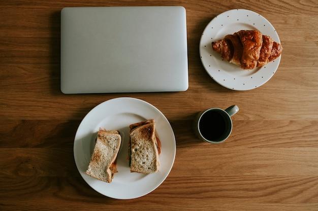 ラップトップのフラットレイとカフェでの朝食