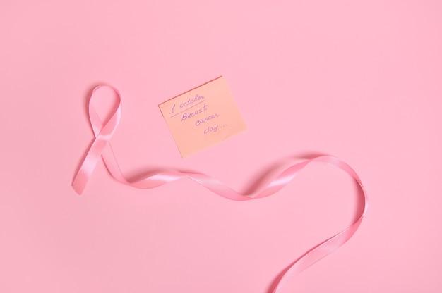 끝이 없는 긴 분홍색 리본과 10월 1일 유방암 인식의 날이라는 글자가 있는 종이 메모는 텍스트를 위한 공간이 있는 분홍색 배경에 격리되어 있습니다.
