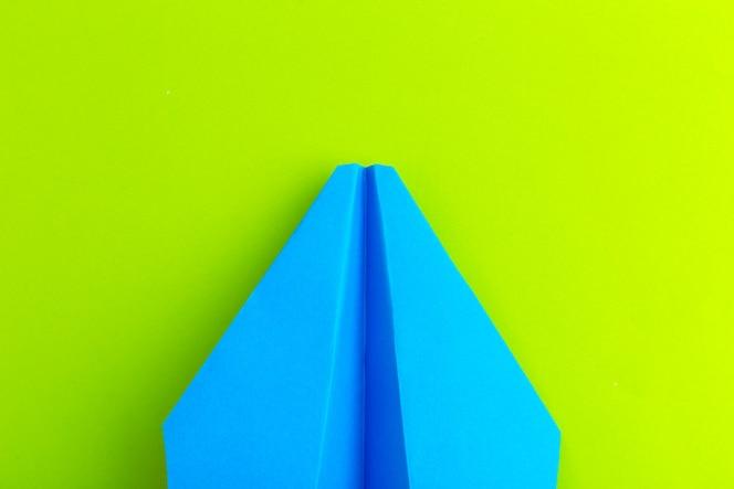 녹색 파스텔 색상 배경에 종이 비행기의 평면 배치