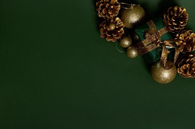 Плоская планировка подарка в блестящей оберточной подарочной бумаге с золотым бантом, сосновыми шишками и золотыми елочными игрушками, разложенными на углу зеленого фона. скопируйте место для рекламы