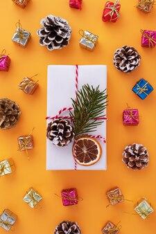 オレンジ色の白い装飾が施されたギフトボックスとクリスマスの装飾のフラットレイ