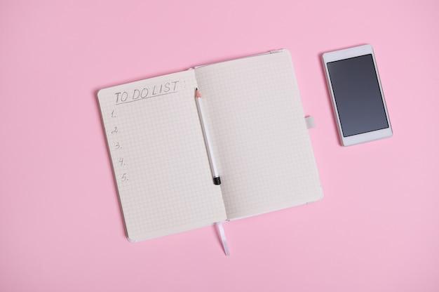 열린 의제, 일기, 복사 공간에 따라 흰색 종이에 할 일 목록이 있는 노트북 한가운데에 있는 연필 옆에 분홍색 배경에 누워 있는 흰색 휴대폰