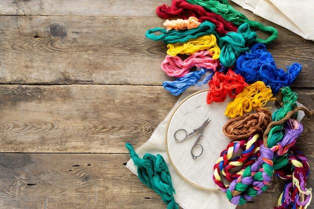 刺繡用アクセサリーのフラットレイ。古い木製のフープ、カラフルなフロスの糸と帆布