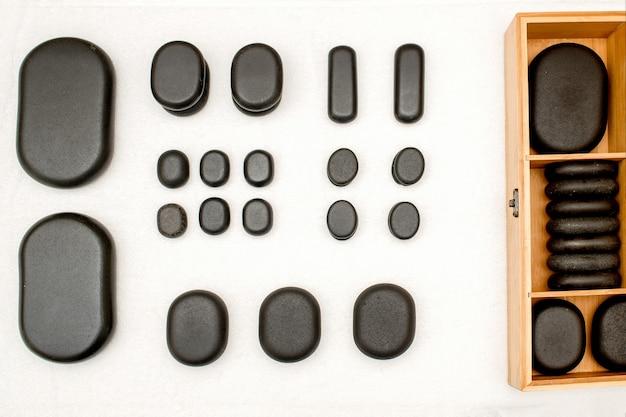 Плоская планировка открытого деревянного ящика со спа-черными камнями на столе в спа-салоне