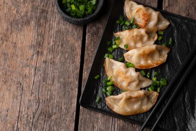 ハーブとコピースペースを備えたアジアの餃子料理のフラットレイ