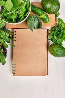 Плоская планировка ассорти из зеленых овощей вокруг кулинарной книги рецептов, бакалейных товаров, местной еды, здоровой чистой еды, вегетарианской и веганской еды, весенней концепции диеты, вида сверху, копировального пространства.
