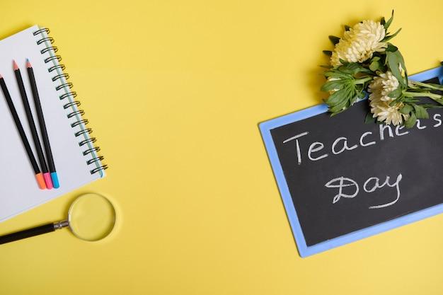 스승의 날이라는 문자가 있는 칠판에 누워 있는 에스터 꽃과 복사 공간이 있는 노란색 배경에 격리된 메모장의 빈 시트에 색연필 옆에 있는 돋보기 확대경