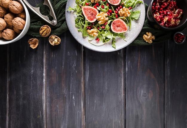 Плоский салат из осеннего инжира на тарелке с копией пространства и грецкими орехами