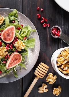 Плоский салат из осеннего инжира на тарелке с грецкими орехами