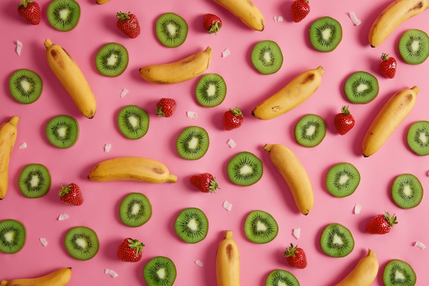 バナナ、キウイ、熟したイチゴのフラットレイは、デザートのトッピング、ジュースやジャムの準備に使用できます。ピンクの背景に健康的なトロピカルフルーツの品揃え。食生活のための新鮮な製品