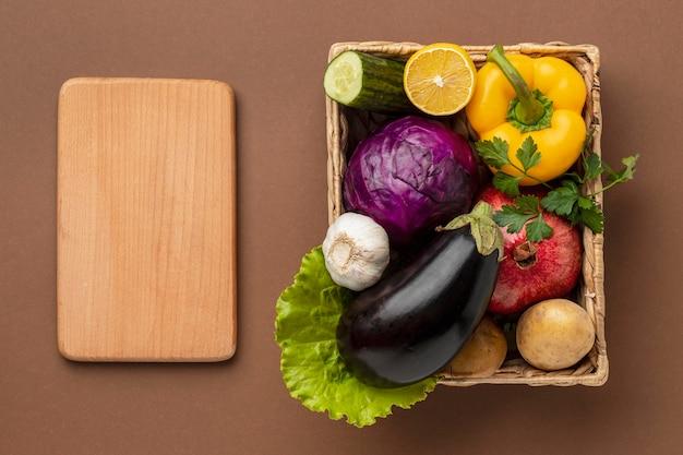 まな板と新鮮な野菜のバスケットのフラットレイ