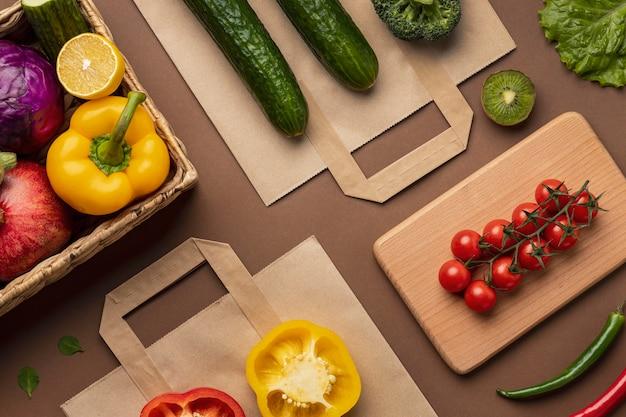 食料品の袋と有機野菜のバスケットのフラットレイ