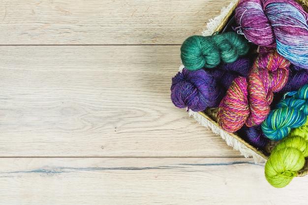 木製のテーブルとコピースペース上のバスケット内の紫と緑の色調で美しいかせのフラットレイアウト