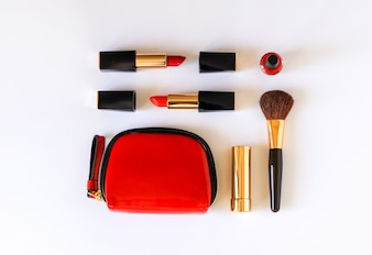 Flat lay of beauty cosmetic products in red, black and gold color knolled