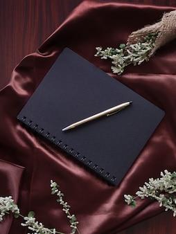 Плоский слой черной ручки дневника и весенних цветов на коричневой атласной ткани
