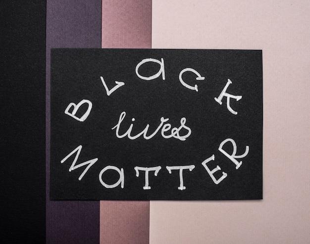 色とりどりの紙に黒い生命問題カードのフラットレイ