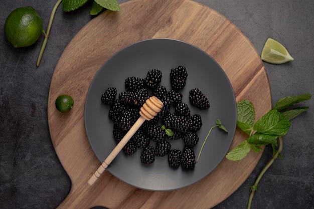 Плоская кладка ежевики на тарелку с мятой и лаймами