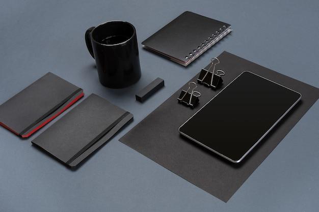 Плоская планировка из чистого листа черной бумаги, черных канцелярских принадлежностей и чашки кофе на сером рабочем столе, макет