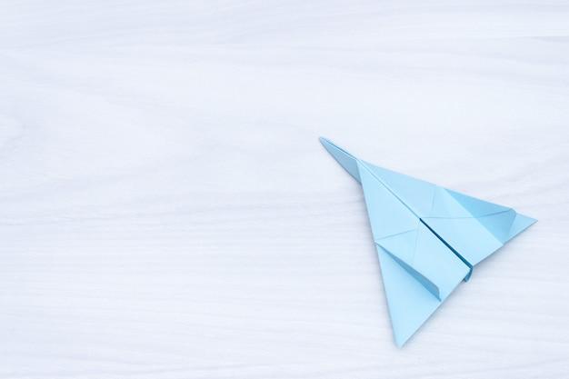 Плоское положение плоскости голубой бумаги на белом фоне деревянные.