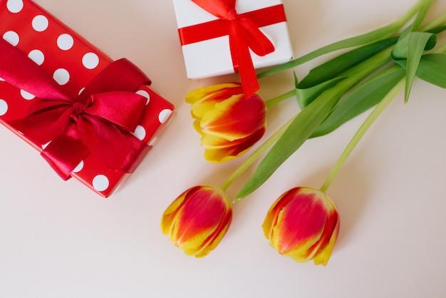 花瓶とテーブルの上のギフトボックスの美しい春のチューリップの花束のフラットレイ